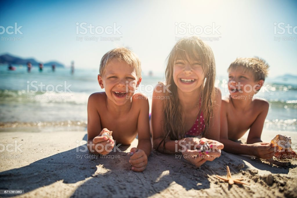 Kids playing with sea shells on sandy beach stock photo