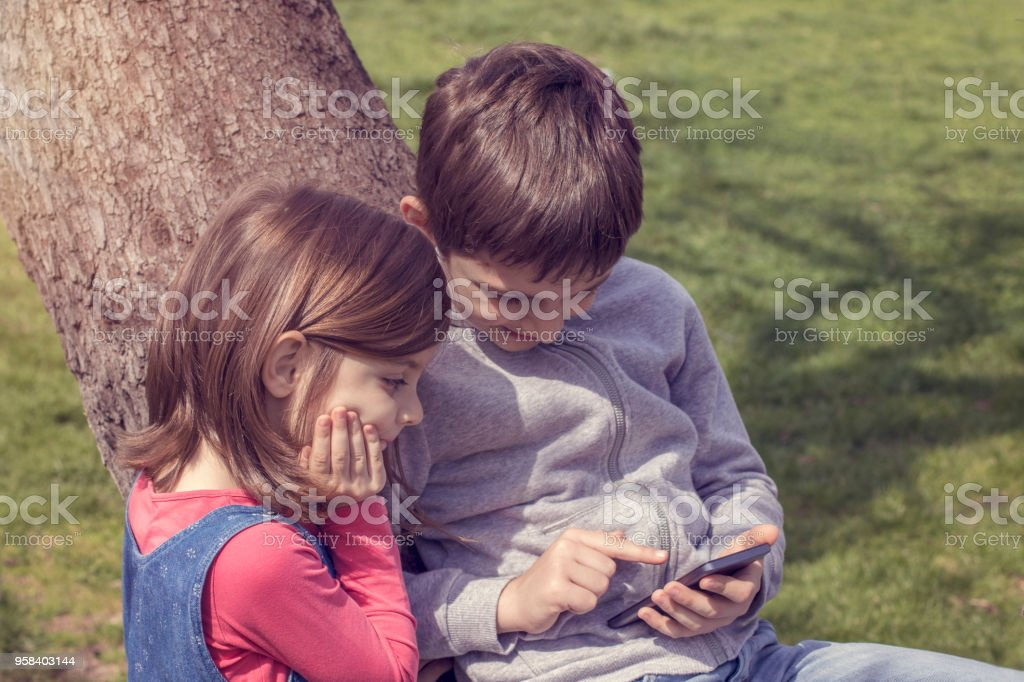 Kids playing with smart phone stock photo