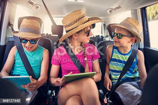 istock Kids playing with tablets during car trip. 948127440