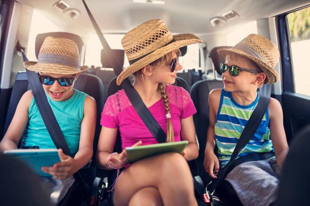 Kinder spielen mit Tabletten während der Autofahrt. – Foto