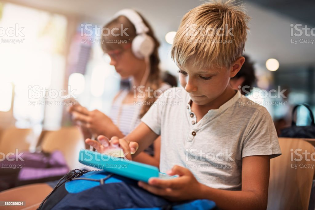 Kids playing with tablets while waiting at the airport stock photo