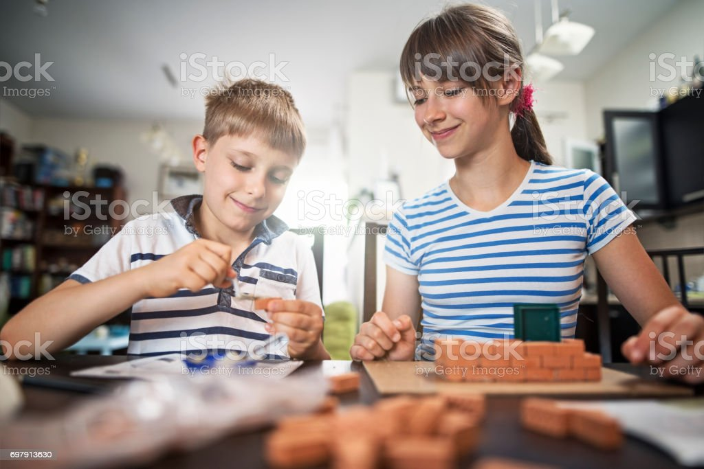 Kids playing with toy bricks at home stock photo