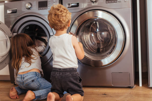 kids playing with washing machine at home - laundry laundry room stock pictures, royalty-free photos & images