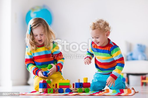 istock Kids playing with wooden toy train 500464760