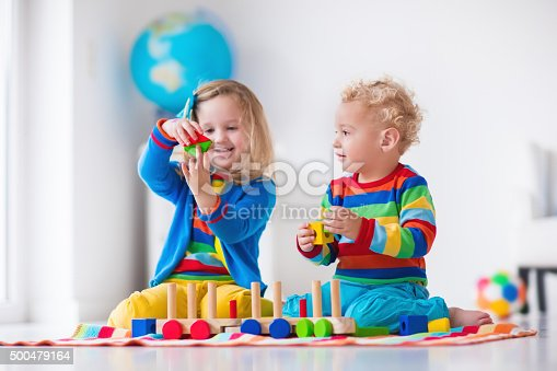 istock Kids playing with wooden toy train 500479164