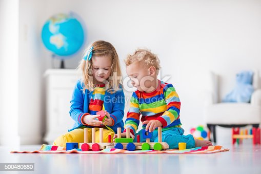istock Kids playing with wooden toy train 500480660