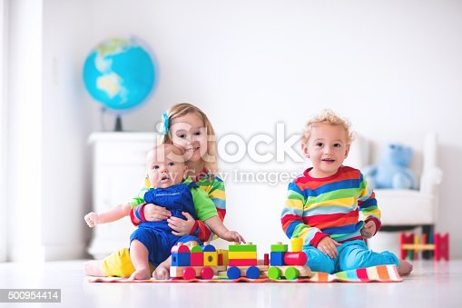 istock Kids playing with wooden toy train 500954414
