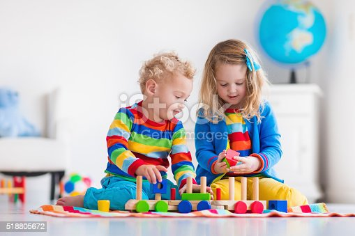 istock Kids playing with wooden toy train 518805672