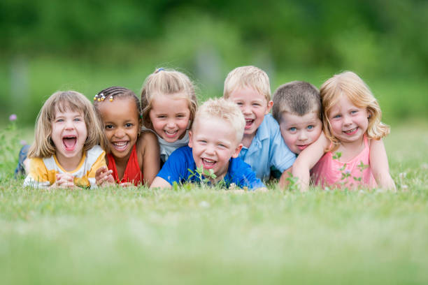 Kids Portrait A multi-ethnic group of preschool children are outdoors in a field. They are wearing casual clothing.  They are lying in the grass and posing for a group portrait. They are all laughing. preschool age stock pictures, royalty-free photos & images