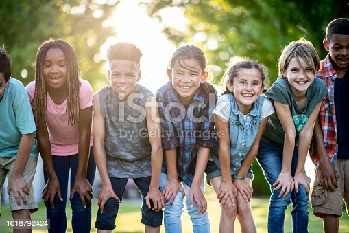A group of kids are outdoors on a sunny day. They are posing with their hands on their knees for a fun group photo.