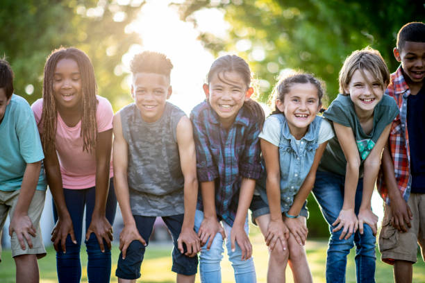 Kids Posing Outside A group of kids are outdoors on a sunny day. They are posing with their hands on their knees for a fun group photo. pre adolescent child stock pictures, royalty-free photos & images