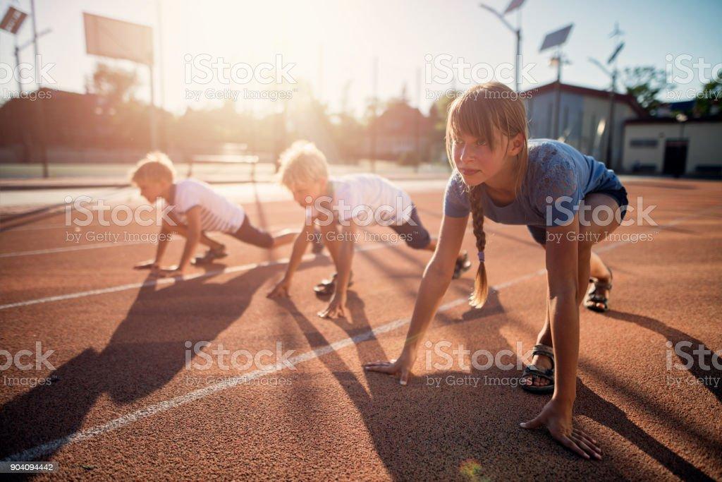 Niños preparándose para pista corren carrera - foto de stock