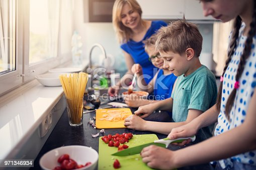 Three kids are cooking today! Mother is overseeing as a teenage girl and her two brother are chopping and mixing ingredients for family lunch. Nikon D850