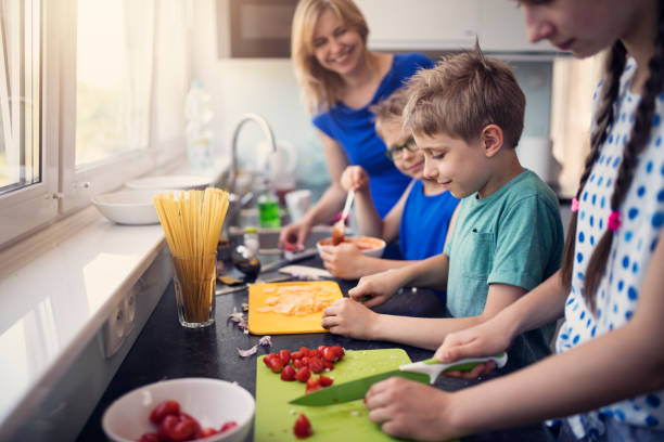 Kids preparing lunch Three kids are cooking today! Mother is overseeing as a teenage girl and her two brother are chopping and mixing ingredients for family lunch. Nikon D850 preparing food stock pictures, royalty-free photos & images