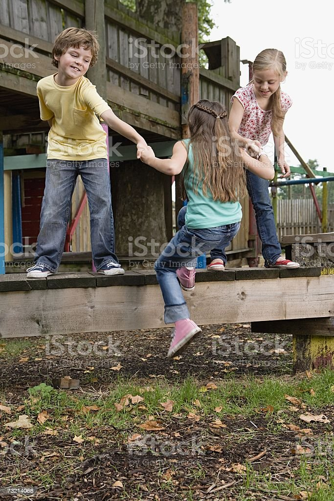 Kids pulling friend onto climbing frame royalty-free stock photo