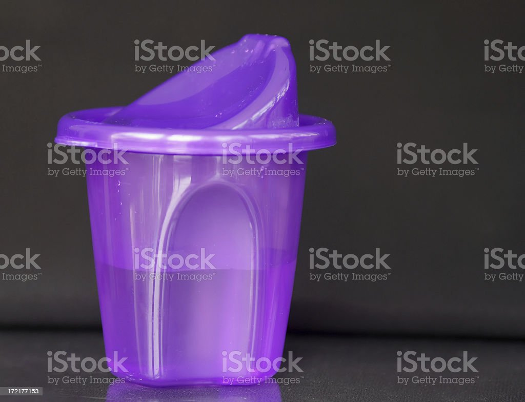 Kid\'s plastic sippy cup on black background.