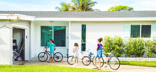 Kids put their bikes away in the garage of their single family home stock photo