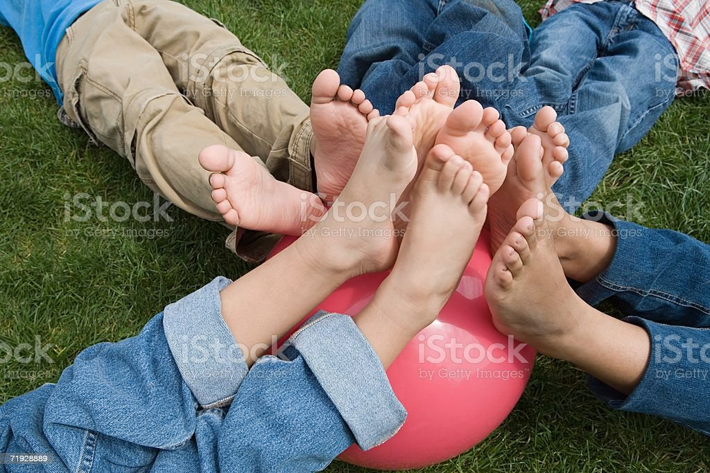 Kinder bringen Ihre Füße am Strand ball – Foto