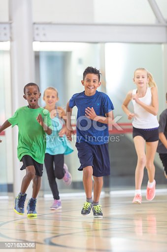 A group of kids are in a gym and wearing sportswear. They are running towards the camera.