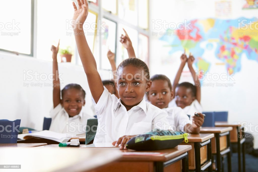 Kids raising hands during a lesson at an elementary school stock photo