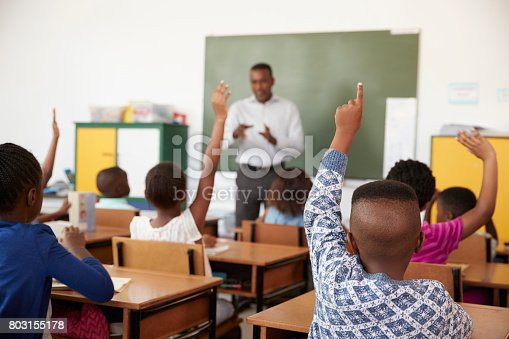 istock Kids raising hands during a lesson at an elementary school 803155178