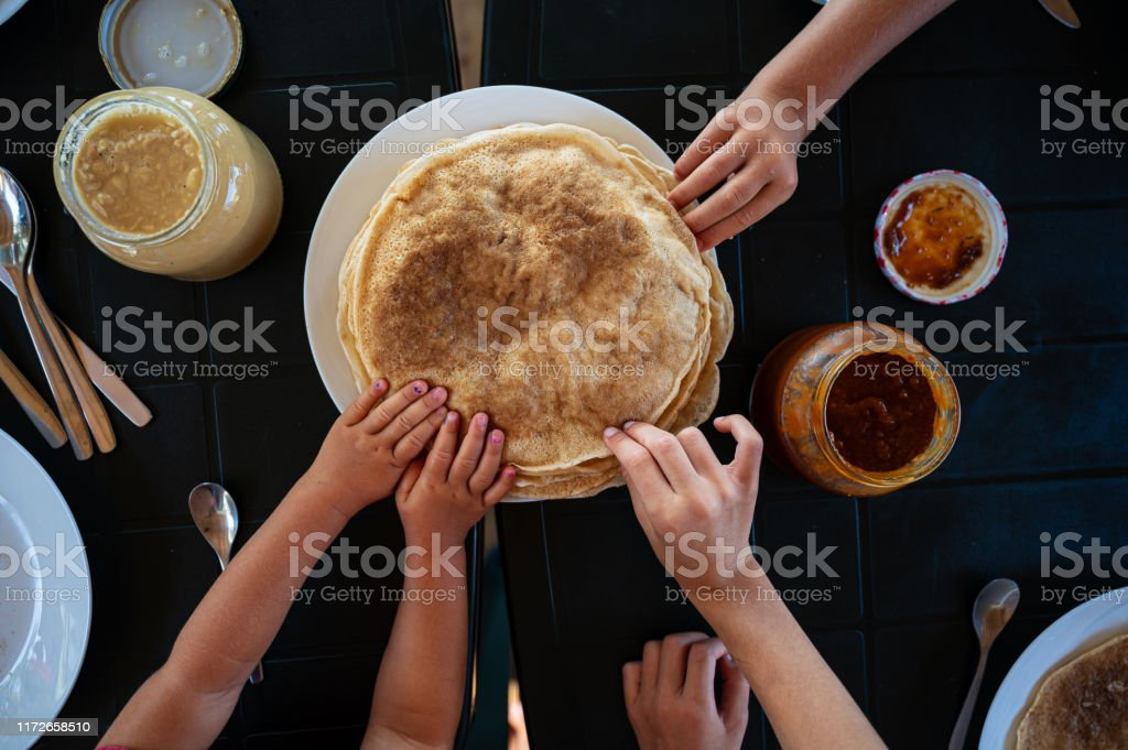 Kids reaching for crepes at breakfast Top view of kids reaching for crepes at a breakfast table. Baked Stock Photo