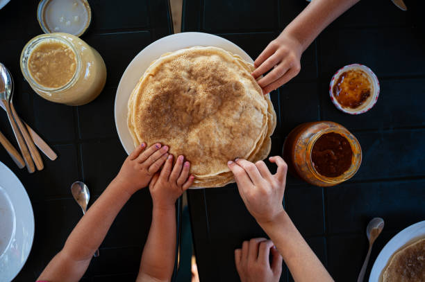 Kids reaching for crepes at breakfast stock photo
