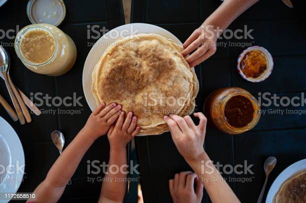 Kids Reaching For Crepes At Breakfast Stock Photo - Download Image Now