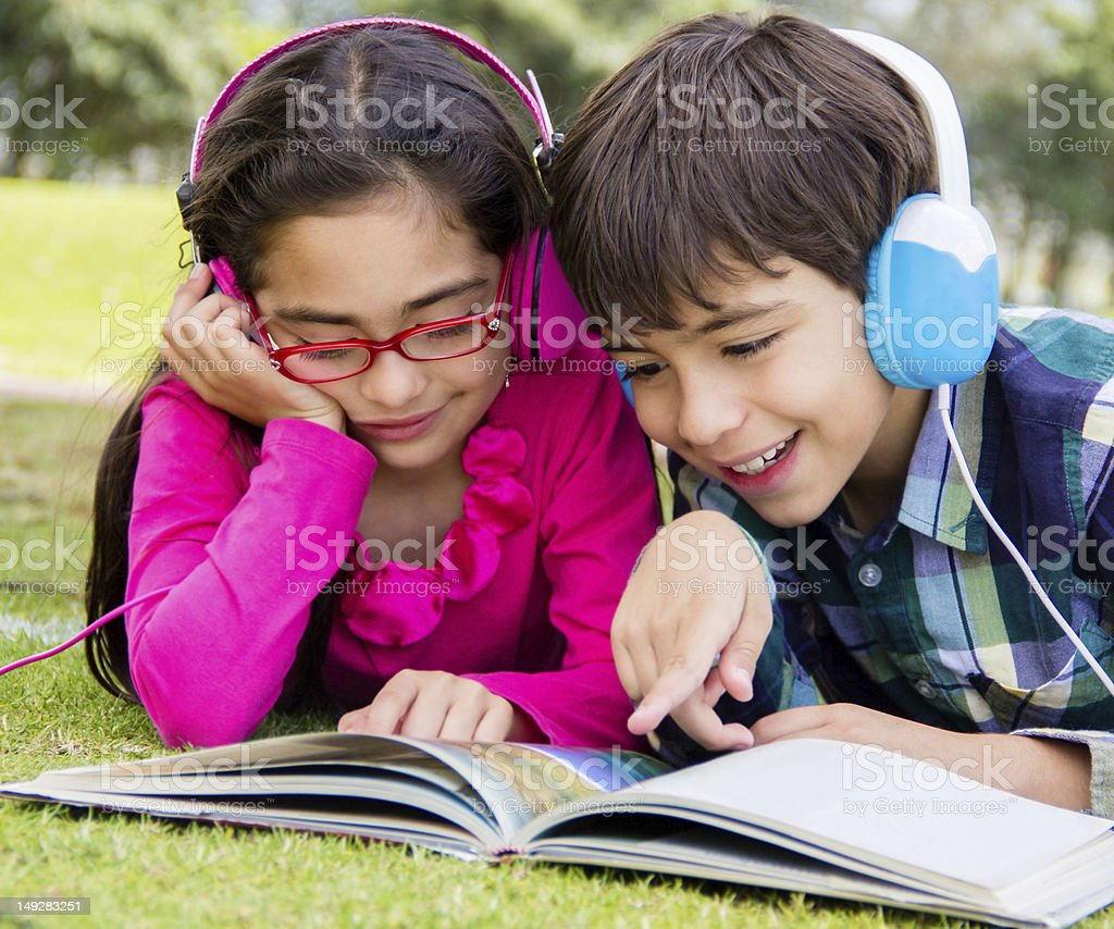 Kids reading at the park stock photo