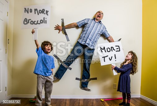 A son and a daughter have hung their father on the wall with duct tape and keep him as a hostage while they are holding placards saying