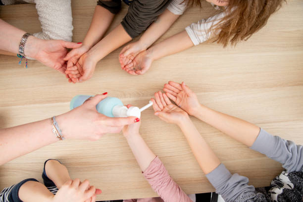 Kids receiving Hand Sanitizer in the classroom stock photo
