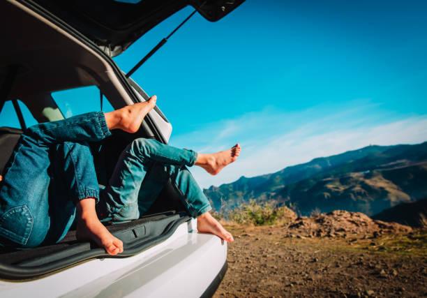 Kinder entspannen sich auf der Autofahrt in der Natur, Familienurlaub in den Bergen – Foto
