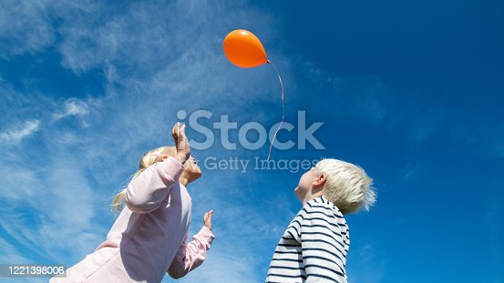 Low angle view of boy and girl releasing orange balloon in blue sky.