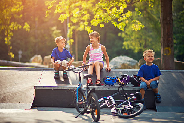 Kids resting after riding bicycles on ramps Little girl and her brothers are resting on a ramp after riding bikes on ramps. Bikes and helmets are lying near. Kids are aged 9 and 5 female biker resting stock pictures, royalty-free photos & images