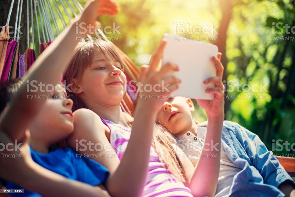 Kids resting on hammock and playing with tablet stock photo