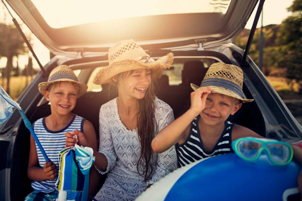 Kids returning from beach by car stock photo