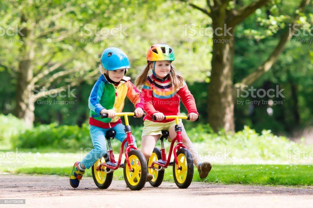 Kids ride balance bike in park stock photo