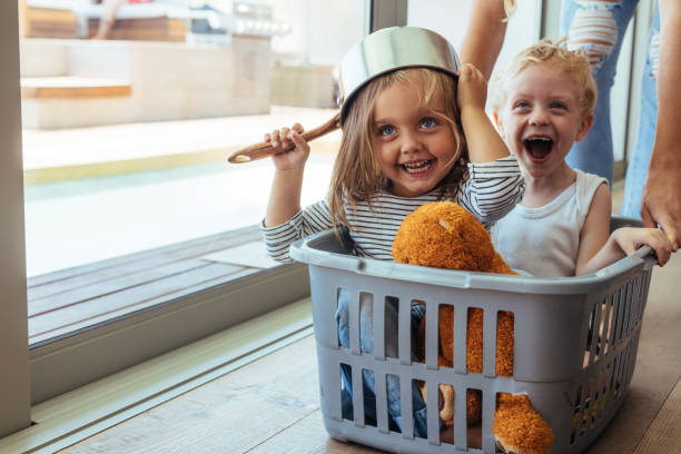 Kids rides in a laundry basket Excited children sitting in a washing basket being pushed by mother. Girl wearing a bowl as helmet with boy laughing. laundry basket stock pictures, royalty-free photos & images