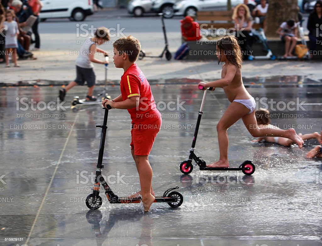 Kids rides on scooters among fountains of Republic Square on weekend stock photo