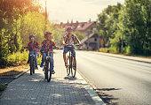 Three kids riding bikes to school.\nNikon D850
