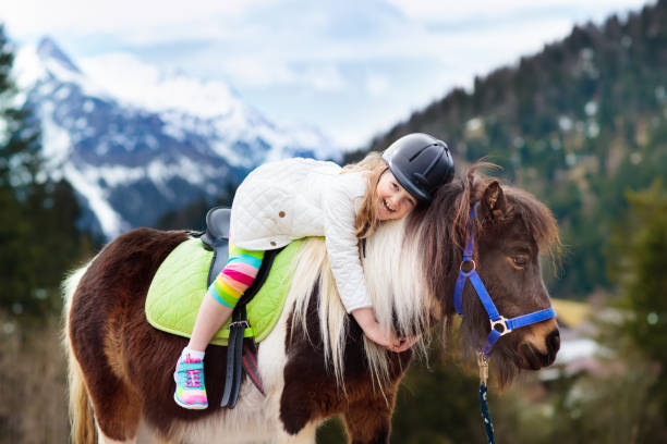 Kids riding pony. Child on horse in Alps mountains Kids riding pony in the Alps mountains. Family spring vacation on horse ranch in Austria, Tirol. Children ride horses. Kid taking care of animal. Child and pet. Little girl in saddle on pony. pony stock pictures, royalty-free photos & images