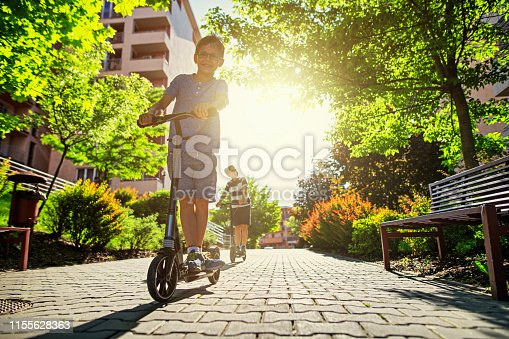 Kids riding scooters in city residential area. Sunny summer day. Nikon D850