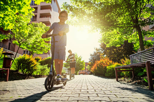 Kids riding scooters in city residential area. Kids riding scooters in city residential area. Sunny summer day. Nikon D850 city life stock pictures, royalty-free photos & images