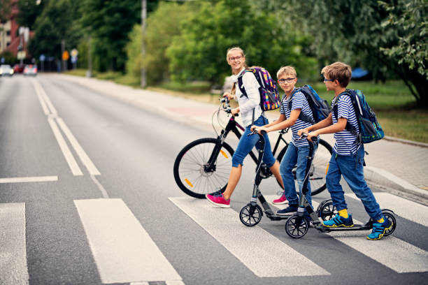Kids riding to school on bike and scooters Three kids riding to school. The kids are wheeling their bike and scooters across zebra crossing. Nikon D850 environmental consciousness stock pictures, royalty-free photos & images