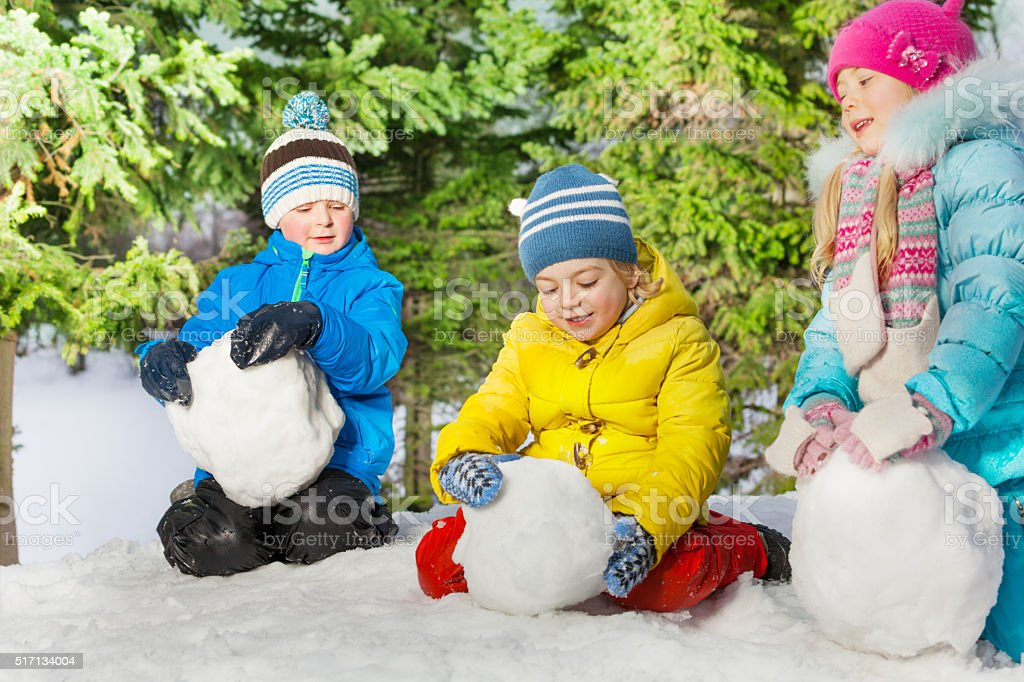 Kids roll snow balls in the park stock photo