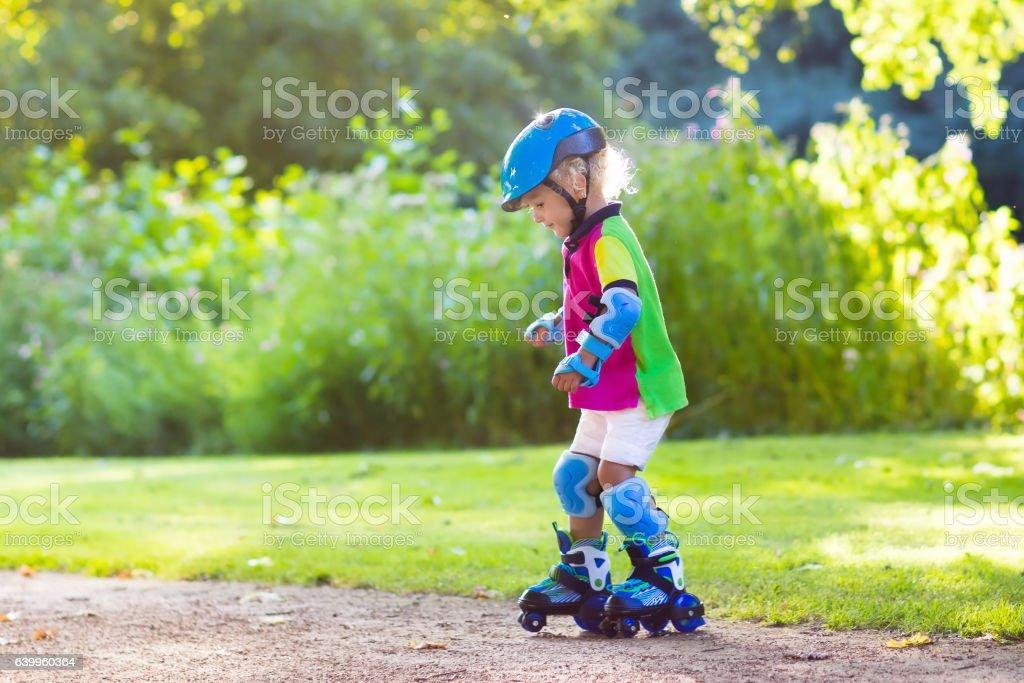 Kids roller skating in summer park stock photo