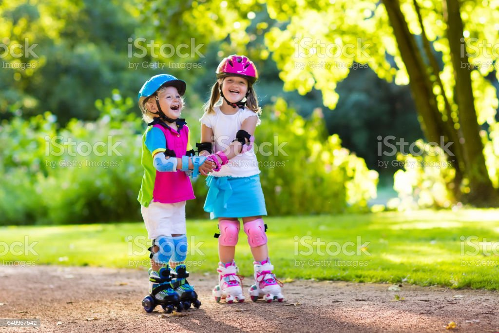 Kids Roller Skating In Summer Park Stock Photo Download Image Now Istock