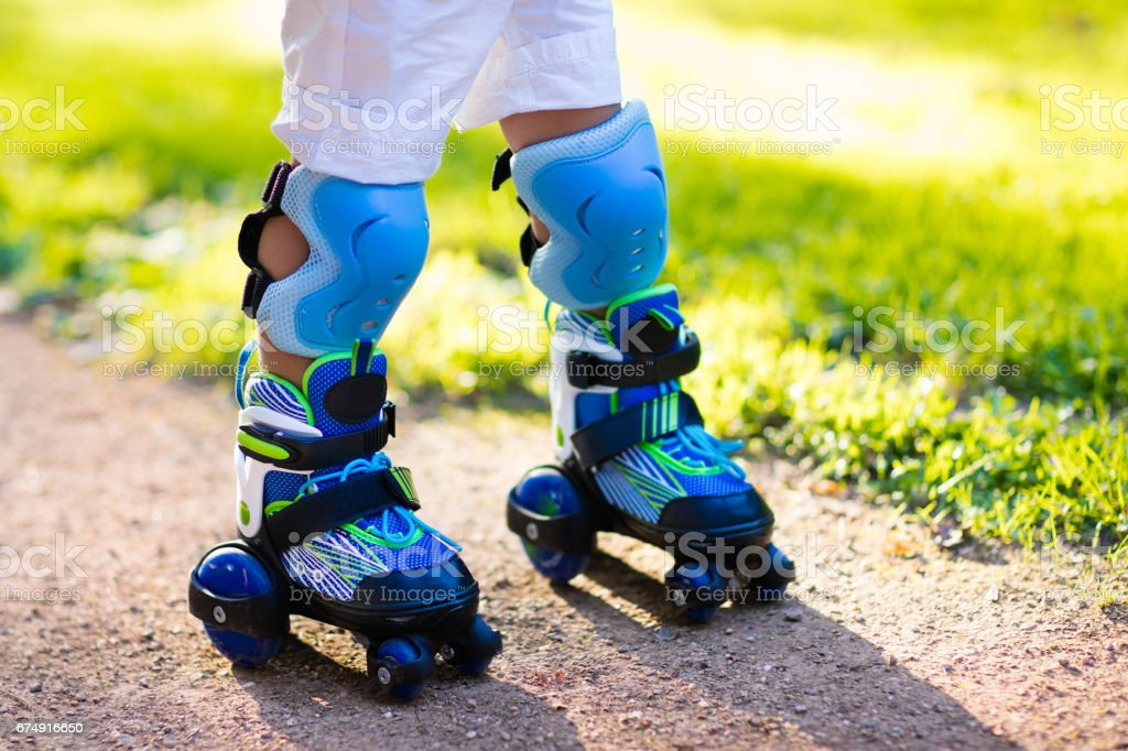 Kids roller skating in summer park royalty-free stock photo