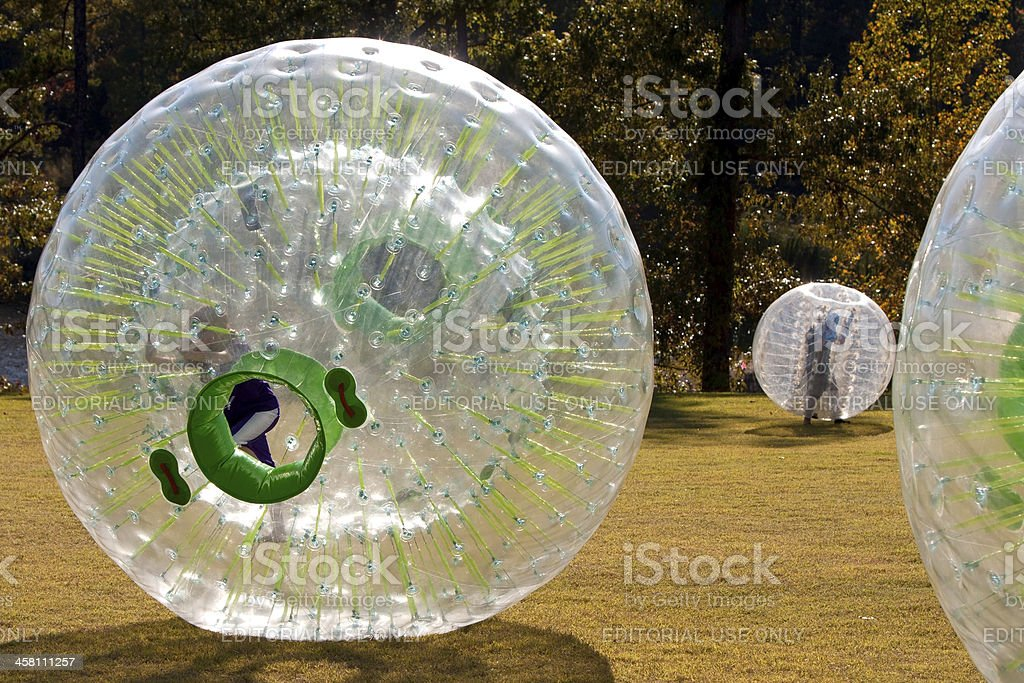 Kids Rolling Around And Playing Inside Large Plastic Balls stock photo