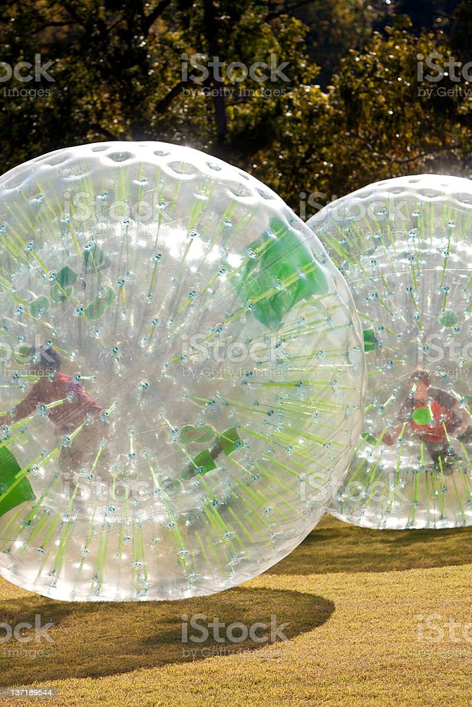 Kids Rolling From Inside Large Plastic Balls stock photo